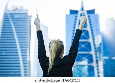 Happy and empowered businesswoman with arms in the air facing the city high-rises. Business success and achievement.