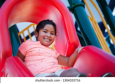 A happy and energetic girl playing on a red playground slide, about to slide down.