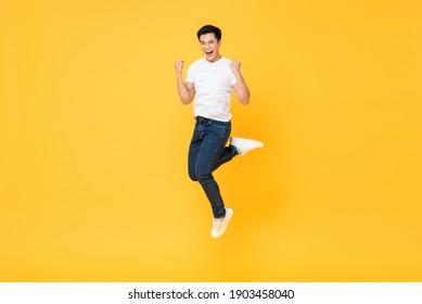 Fröhlicher, dynamischer junger asiatischer Mann, der auf gelbem Studiohintergrund  Fäuste und Schreien springt, selektiver Fokus