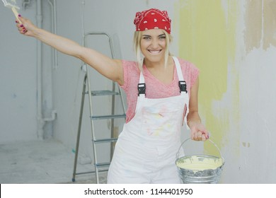 Happy energetic young blond woman in bandana and white overalls holding bucket with pastel yellow wall paint and stretching out hand with brush looking at camera smiling and biting lip.
