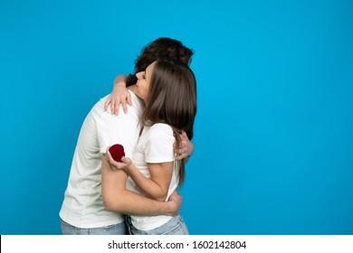 Happy engaged couple embracing isolated on blue background.