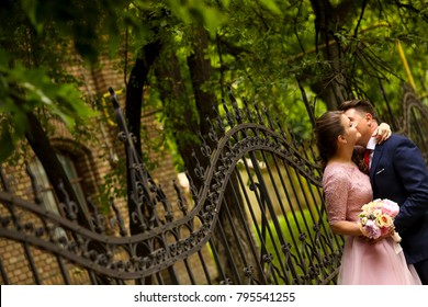 Happy engagement couple in a park with bouquet of flowers