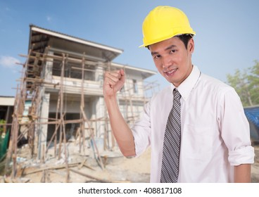 Happy engineer celebrating with arm raised, concept of successful, house construction background