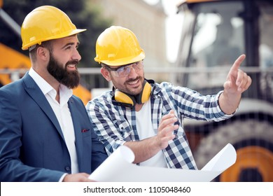 Happy engineer discussing with colleague at construction site on sunny day. They are planing to build.