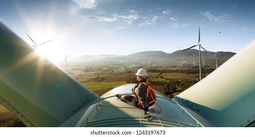 Happy engineer feel success after good work. He standing a top of windmill and looking beautiful sunset landscape - Shutterstock ID 1243197673