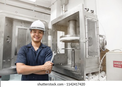 Happy engineer holding a wrench for fix plasma vacuum machine in plasma plant, Asian engineer wear safety helmet and holding a wrench, Industrial technician portrait, Repair, Smiling asian engineer