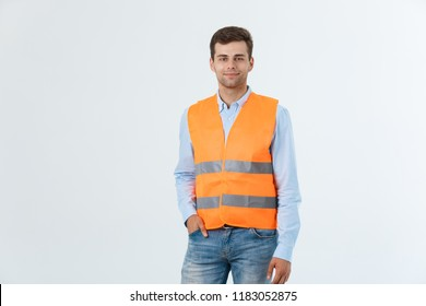 Happy engineer smiling and standing confidently, guy wearing caro shirt and jeans with orange vest, isolated on white background.