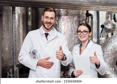 happy engineers showing thumbs up near compressed air system