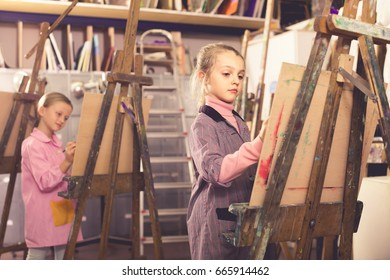 happy english  schoolgirls diligently training their painting skills during class at art studio