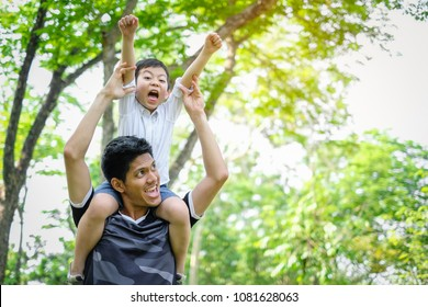 Happy and enjoy Asian Father and son having fun in summer park