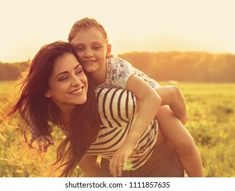 Happy enjoying loving mother hugging her playful laughing kid girl on sunset bright summer background. Closeup toned color bright portrait.