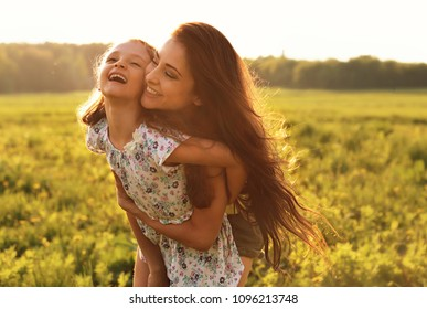 Happy enjoying mother hugging her laughing kid girl on sunset bright summer background. Closeup portrait.