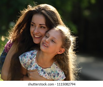 Happy enjoying mother hugging her relaxing smiling kid girl on bright summer background. Closeup portrait of love.