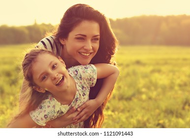 Happy enjoying mother hugging her relaxing joying kid girl on sunset bright summer background. Closeup toned color portrait of love.