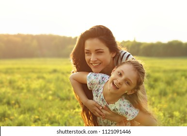 Happy enjoying mother hugging her relaxing joying kid girl on sunset bright summer background. Closeup color portrait of love.