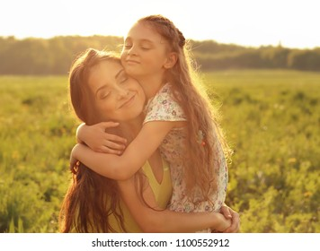 Happy enjoying mother strong hugging her relaxing kid girl on sunset bright summer background. Closeup portrait of love.