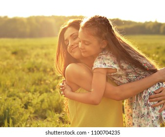 Happy enjoying mother strong hugging her relaxing kid girl on sunset bright summer background with closed eyes. Closeup portrait of family love.