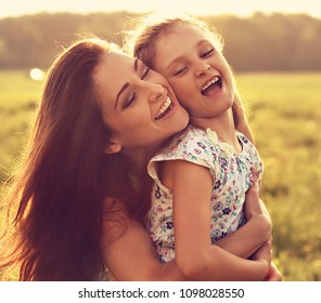 Happy enjoying smiling mother hugging her playful laughing kid girl on sunset bright summer background. Closeup toned portrait