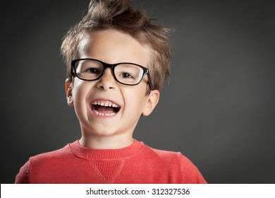 Happy enthusiastic boy. Studio shot portrait over gray background. Fashionable little boy.