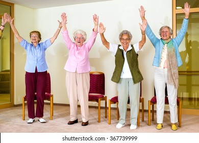 Happy enthusiastic group of senior women doing a physical workout in a seniors gym standing laughing and smiling with their hands raised into the air