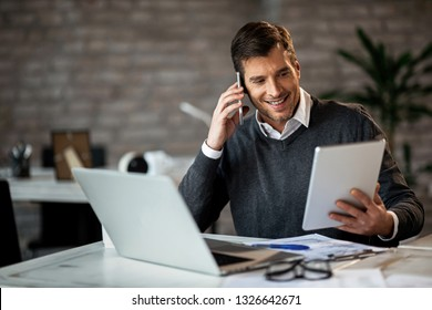 Happy entrepreneur communicating over mobile phone while working on touchpad in the office.