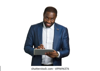 Happy entrepreneur with digital tablet. Smiling young businessman working at portable computer tablet and looking straight. Project manager working on touch screen computer.