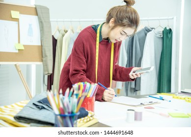 Happy entrepreneur fashion designer in textile business designing new retail clothing collection. Happy working woman seamstress , designer enjoy working on fabric sketches. entrepreneur concept