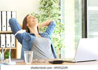 Happy entrepreneur resting sitting on a chair at office with a window in the background