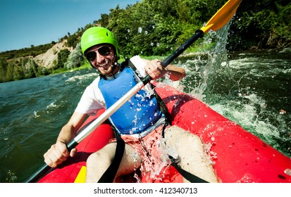 A happy entusiastic male in red inflatable canoe having a fun ride in calm waters of a river.