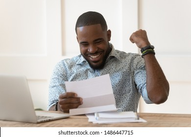 Happy euphoric young african american guy received paper report, university admission letter, celebrating important goal achievement, banking loan approval, full credit repayment, lottery win notice.