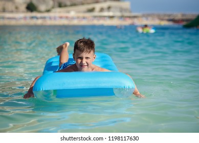 Happy European boy in striped swimming shorts is laying on a blue floater in the ocean. He is enjoying his holidays and smiling.