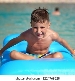Happy European boy in striped swimming shorts is sitting on a blue floater in the ocean. He is enjoying his holidays and attractively smiling to the camera.