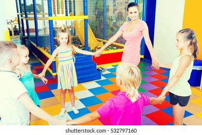happy european children dancing with teacher to music in class at school