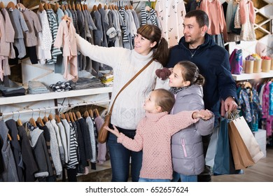 Happy european family with daughters showing their purchases in childrenâ??s clothes shop