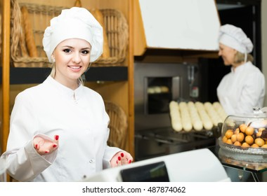 happy european female cooks with fresh and tasty bread in bakery