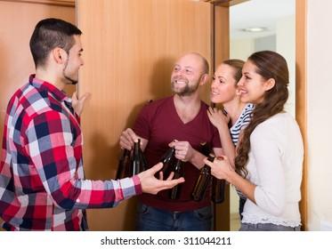 Happy european guests with bottles standing in doorway and smiling