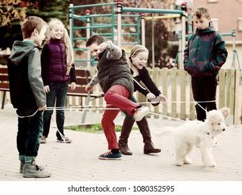 happy european  kids skipping on chinese jumping elastic rope in yard