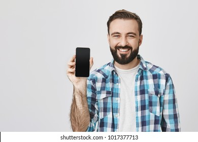 Happy european man with beard and moustache showing smarphone to camera while smiling broadly during advertising. Blogger makes video of new gadget of his favorite company