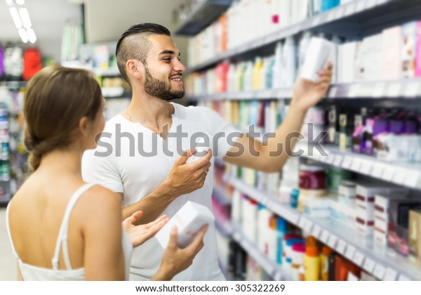 happy european man buying cosmetical cream in the shopping mall