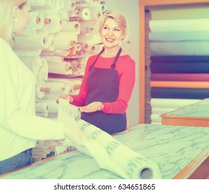 happy european mature female seller offering fabrics to young woman in textile shop