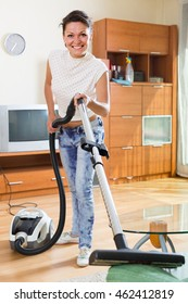 Happy european middle-aged woman hoovering apartment