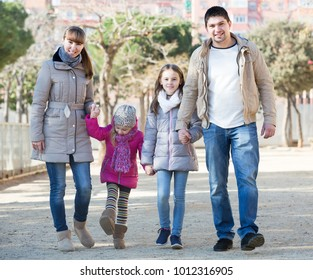 Happy european  parents and little daughters taking a walk in park