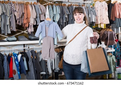 happy european pregnant woman showing her purchases in children's clothes shop