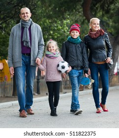 happy european spouses with children posing in autumn park and smiling