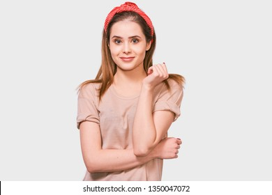 Happy European woman smiling, feels excitement, being in high spirit, posing against white background. Pretty female has joyful expression wearing red headband.