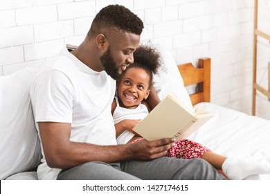 Happy evening. African american man reading fairy tale to his little daughter, sitting in bedroom, empty space