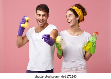 Happy excied man with stubble wearing rubber gloves, pointing finger at camera, his girlfriend standing next to him, smiling, holding sponge and cleanser spray, both ready for overall cleaning up