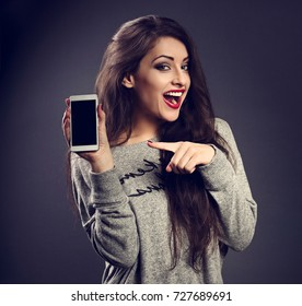 Happy excite beautiful makeup woman holding and advertising mobile phone and showing on it the finger on grey dark background. Toned closeup portrait
