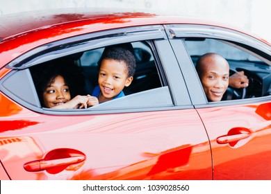 Happy and excited African American family taking a road trip with their car - Happy family togetherness concept