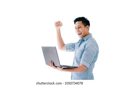 Happy excited Asian man holding laptop and raising his arm up to celebrate success or achievement isolated on white. image with clipping path.